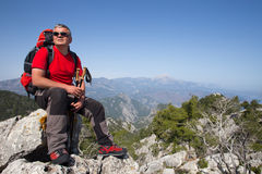 Hiker standing on top of the mountain with valley on the background. Stock Photo