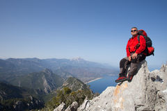 Hiker standing on top of the mountain with valley on the background. Stock Images