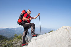 Hiker standing on top of the mountain with valley on the background. Royalty Free Stock Photo