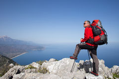 Hiker standing on top of the mountain with valley on the background. Royalty Free Stock Photography