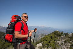 Hiker standing on top of the mountain with valley on the background. Royalty Free Stock Photos