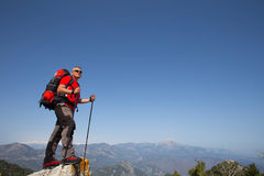 Hiker standing on top of the mountain with valley on the background. Stock Image