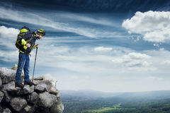 Hiker standing on the top of rock Stock Photography