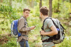 Hiker standing in the woods with a friend and looking at the cam Royalty Free Stock Image