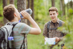 Hiker standing in the woods with a friend and looking at the cam Royalty Free Stock Images