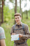 Hiker standing in the woods with a friend and looking at the cam Stock Image