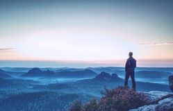 Hiker stands and enjoys valley view from hill stock image