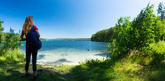 Hiker stands on the green coast. Of a crystal clear lake. Lake of Turgoyak, Russia stock photography