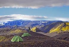 Hiker stands near a tent  and enjoying the summer sunrise Stock Photos