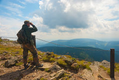 Hiker stands on a peak. And enjoy the scenery through binoculars Royalty Free Stock Photography