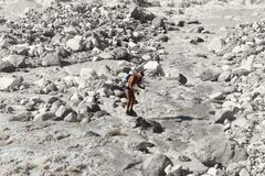 Hiker stands on a rock in the midst of a raging mountain river. Athletic build, power, strength and desire are guessed in his pose. Around there is a stony Royalty Free Stock Images