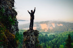 Hiker stands on top of the mountain, hands raised up