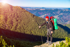 Hiker Staying on High Rock and Mountain View with Autumnal Forest Royalty Free Stock Images