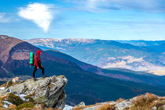 Hiker staying on rocky Cliff observing Mountains Panoramic View Royalty Free Stock Photos