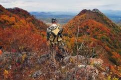 Hiker stays on big rock Stock Images