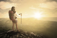 Hiker with stick on mountain. Rear view of female hiker standing on the mountain peak while carrying backpack and holds a stick Stock Photography