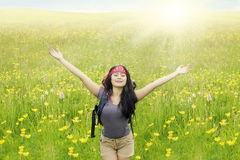 Hiker stretching hands on blossom meadow Stock Photo