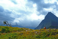 Hiker strolls along a trail in Glacier National Park. Royalty Free Stock Image