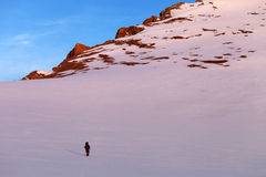 Hiker in sunrise snowy mountains Royalty Free Stock Photos