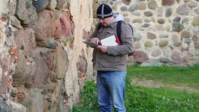 Hiker with tablet PC and backpack near ancient wall stock footage