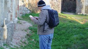 Hiker with tablet PC and backpack in ruins stock video