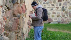 Hiker with tablet PC near ancient wall stock video