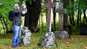 Hiker with tablet PC near old stone crosses stock footage