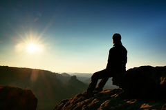 Hiker take relaxing on a rock and enjoying sunset at horizon. Vivid effect. Stock Image