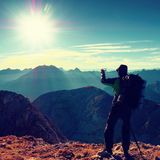 Hiker takes phone photo. Man on Alps mountain peak.View to blue foggy valley Royalty Free Stock Photo