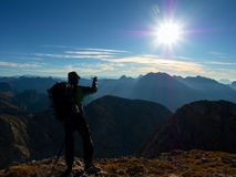 Hiker takes phone photo. Man on Alps mountain peak.View to blue foggy valley Stock Image