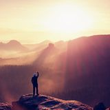 Hiker takes photo by smart phone on the peak of mountain at spring sunrise. Sharp cliff above deep forest valley. Royalty Free Stock Images