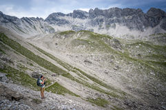 Hiker takes pictures on a mountain pass of the Allgau Alps. In Bavaria, Germany Royalty Free Stock Photos