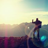 Hiker takes selfie photo. Man with big backpack and poles walk on Alpine mountain Royalty Free Stock Photo