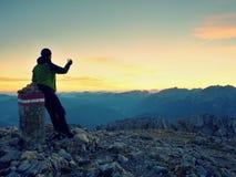 Hiker takes selfie photo. Man  sit on Austria Germany border stone on Alpine mountain. Stock Photos