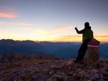 Hiker takes selfie photo. Man  sit on Austria Germany border stone on Alpine mountain. Stock Photo