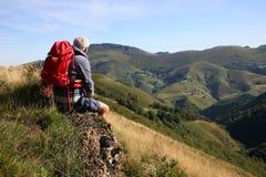 Hiker taking a break admiring beautiful mountains Royalty Free Stock Images