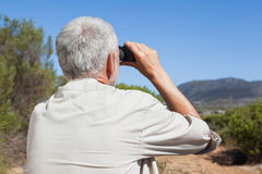 Hiker taking a break on country trail looking through binoculars Royalty Free Stock Image