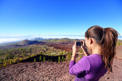 Hiker taking landscape picture on top of mountain Stock Images