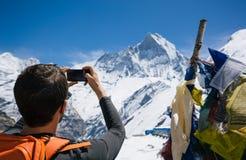 Hiker taking photo of Himalayan summit Royalty Free Stock Photos