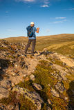 Hiker taking photo of mountain landscape with smartphone Royalty Free Stock Images