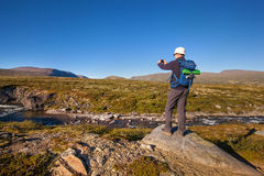 Hiker taking photo of mountain landscape with smartphone Royalty Free Stock Photography