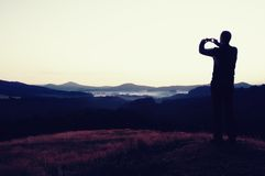 Hiker is taking photo of sunrise by smart phone on meadow. View to hilly landscape. Stock Images