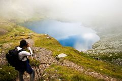Hiker taking photos at Capra lake in Fagaras Royalty Free Stock Images