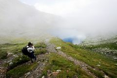Hiker taking photos at Capra lake in Fagaras Stock Photo