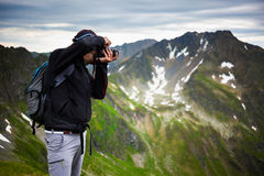 Hiker taking photos of landscape. Hiking tourist taking photos of the alpine landscape Stock Photography