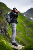 Hiker taking photos of landscape Stock Photo