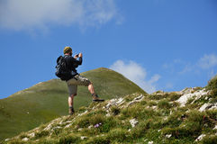 Hiker taking photos on mountain Stock Photo