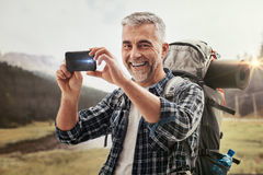 Hiker taking pictures with a smartphone Royalty Free Stock Images