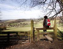 Hiker taking a rest. Lady Hiker Sitting in a Stile Viewing an English Rural Landscape Royalty Free Stock Image