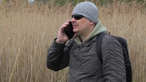 Hiker talking on cell phone near cane stock footage